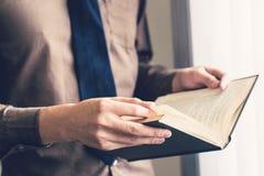 Geschäftsmannhand, die Buch hält und am Fenster liest lizenzfreie stockfotos