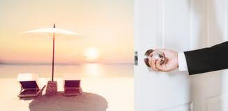 Geschäftsmannhand, die den Türknauf, öffnend zum tropischen Strand im Sonnenuntergang mit Strandstühlen und -regenschirm, Weinles Stockfotografie