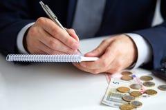 Geschäftsmannhand, die ein Stiftschreiben auf Notizblock hält Stockbilder