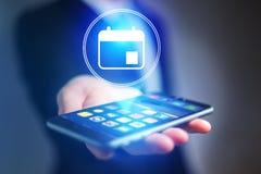 Geschäftsmannhand, die Handy mit Kalenderikone hält Lizenzfreie Stockfotos
