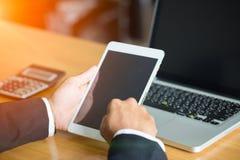 Geschäftsmannhand, die an intelligentem Telefon und Laptop-Computer arbeitet lizenzfreie stockbilder