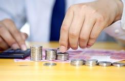Geschäftsmannhand, die Münzen stapelt Stockfotografie