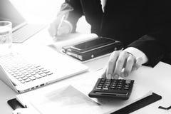 Geschäftsmannhand, die mit Finanzen über Kosten und Taschenrechner arbeitet Lizenzfreie Stockbilder