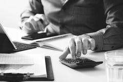 Geschäftsmannhand, die mit Finanzen über Kosten und Taschenrechner arbeitet Lizenzfreie Stockfotografie