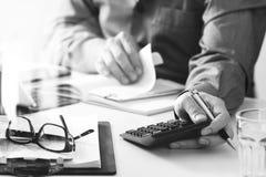 Geschäftsmannhand, die mit Finanzen über Kosten und Taschenrechner arbeitet Lizenzfreie Stockfotos