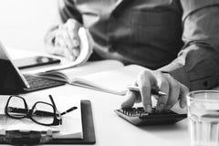 Geschäftsmannhand, die mit Finanzen über Kosten und Taschenrechner arbeitet Stockfotografie