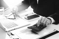 Geschäftsmannhand, die mit Finanzen über Kosten und Taschenrechner arbeitet Lizenzfreies Stockbild