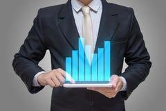 Geschäftsmannhand, die Tablettendiagrammfinanzierung auf grauem Hintergrund hält Stockbild