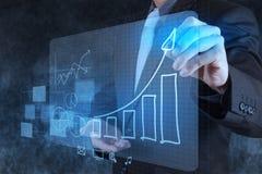 Geschäftsmannhand, die virtuelles Diagrammgeschäft zeichnet Stockfotos