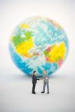 Geschäftsmannhand, die vor dem globalen rüttelt Lizenzfreie Stockfotos