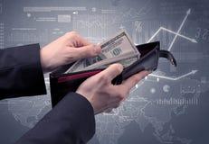 Geschäftsmannhand nimmt Dollar von der Geldbörse heraus Stockfotografie