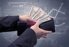 Geschäftsmannhand nimmt Dollar von der Geldbörse heraus Stockbild