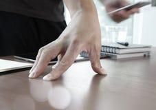 Geschäftsmannhand unter Verwendung des Laptops und des Handys Stockbilder