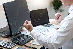 Geschäftsmannhandel auf Lager on-line--, Börsenmakler, die das Diagramm betrachtet, das mit Bildschirm und glücklich, auf a zu be lizenzfreie stockbilder
