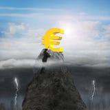 Geschäftsmannhandfehlendes Eurosymbol auf Spitze mit sonnigem stürmischem Lizenzfreie Stockfotografie