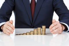 Geschäftsmannhandschützende Münzen am Schreibtisch Stockfotos