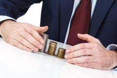 Geschäftsmannhandschützende Münzen am Schreibtisch Stockfoto