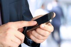Geschäftsmannholding und Anwendung des Handys Stockfotos