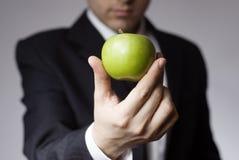 Geschäftsmannholdingapfel Stockfoto