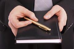 Geschäftsmannholdingtagesordnung und goldene Feder Lizenzfreie Stockfotografie