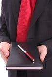 Geschäftsmannholdingtagesordnung und rote Feder Lizenzfreies Stockfoto