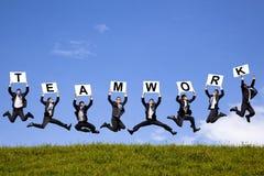 Geschäftsmannholdingteamwork-Text und -c$springen Lizenzfreies Stockfoto