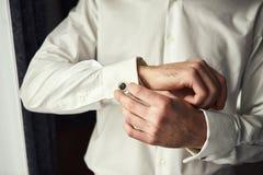 Geschäftsmannkleiderweißhemd, Mann übergibt Nahaufnahme, den Bräutigam, der morgens vor Hochzeitszeremonie fertig wird stockfoto