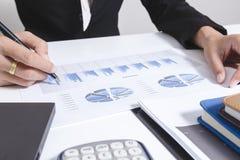 Geschäftsmannkontrolle analysiert ernsthaft die Kollegen eines Finanzberichts-Investors, die Finanzdiagrammdaten des neuen Planes Stockfoto