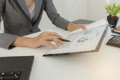 Geschäftsmannkontrollgewinndokument und berechnen ungefähr und merken die Daten, die im Büro gekostet werden Lizenzfreie Stockfotos