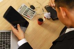 Geschäftsmannkopfschmerzen mit der Hand, die Tablette auf hölzernem Tabellen-DES hält stockfotos