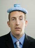 Geschäftsmannkranker mit Eissatz auf Kopf stockbild