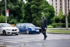 Geschäftsmannkreuz die Straße im Freien mit dem Aktenkoffer, der eine Gasmaske auf dem Gesicht trägt stockbilder