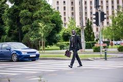Geschäftsmannkreuz die Straße im Freien mit dem Aktenkoffer, der eine Gasmaske trägt stockbild