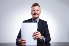 Geschäftsmannlächeln, das Dokumente verwahrt lizenzfreie stockfotos