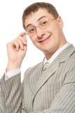 Geschäftsmannlächeln und rührende Gläser Stockfoto