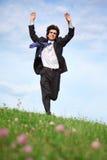 Geschäftsmannlack-läufer auf Gras mit den angehobenen Händen stockfoto