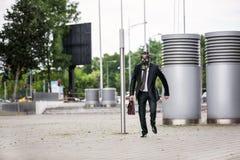 Geschäftsmannlaufen im Freien mit dem Aktenkoffer, der eine Gasmaske trägt stockbilder