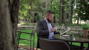 Geschäftsmannlesebuch während coffe Bruches outdoor steadicam Schuss stock footage