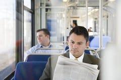 Geschäftsmannlesezeitung auf Zug stockbild