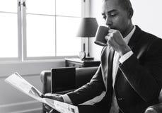 Geschäftsmannlesezeitung und haben Kaffee stockfoto