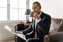 Geschäftsmannlesezeitung und haben Kaffee lizenzfreies stockfoto