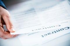 Geschäftsmannlesung durch einen Geschäftsvertrag Stockfotografie