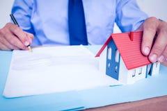 Geschäftsmannlesung und -schreiben ein contrat, bevor es unterzeichnet wird Lizenzfreie Stockfotos