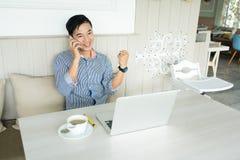 Geschäftsmannlesungssmartphonemitteilung mit glücklichem lächelndem Gesicht, stockfoto