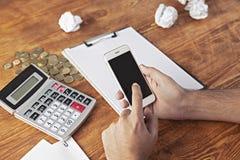 Geschäftsmannmünzen-Taschenrechnertelefon lizenzfreie stockfotos