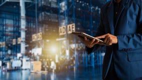 Geschäftsmannmanager, der Tablettenkontrolle und -steuerung für Arbeitskräfte mit modernem Geschäftslager verwendet stockbild