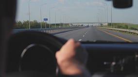 Geschäftsmannmannautofahren, Hand auf dem Lenkrad, vorwärts schauend zur Straße stock video footage