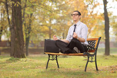 Geschäftsmannmeditieren gesetzt auf einer Bank im Park Stockbild