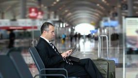 Geschäftsmannpassagier, der Tablet-Computer am Flughafen verwendet stock video footage