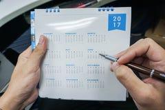 Geschäftsmannplan, der 2017 Kalender trifft Lizenzfreie Stockfotos